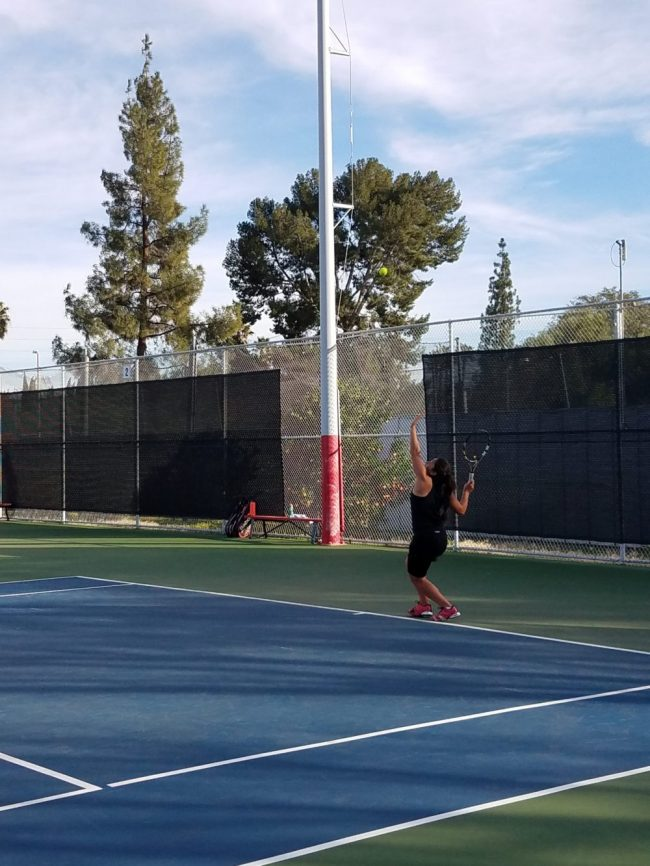 Photo shows female tennis player about to serve the ball