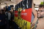 """People hold up a sign that says, """"Resist fascism, learn from history"""""""