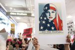 """woman holds up a poster with a woman wearing a US flag hijab that reads """"we the people are greater than fear"""""""