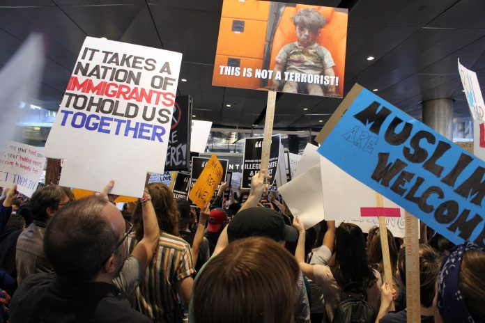People chant and hold up posters in protest of the Muslim ban