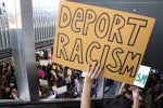 """Person holds up a sign which says, """"deport racism"""""""