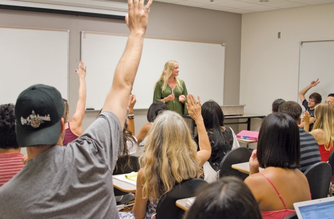 Students pictured raising their hands in Jeanine MingA's communications class