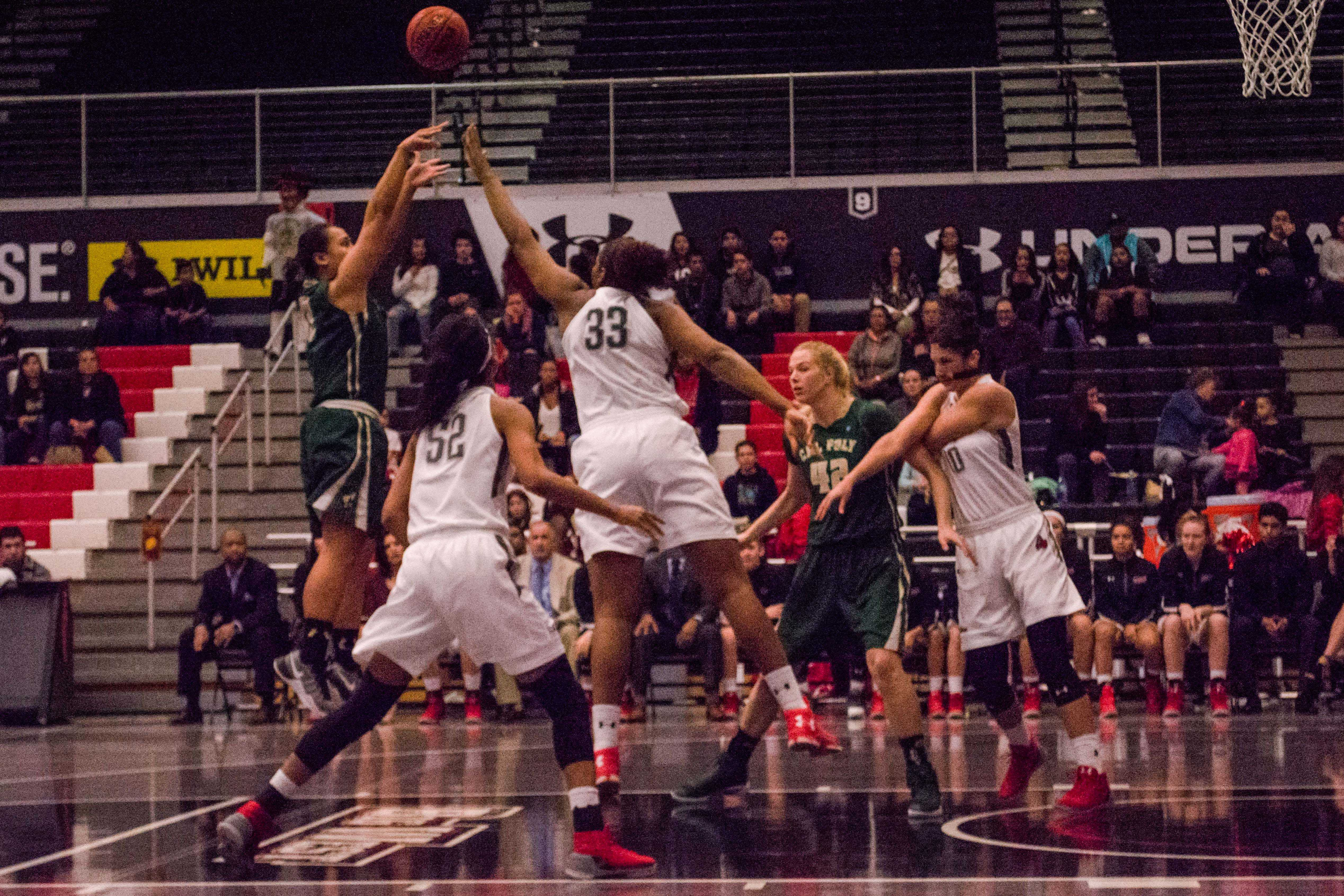CSUN's women's basketball team defends as Cal Poly's Dynn Leaupepe (far left, junior, number 13) takes a shot. Photo credit: Emily Pierce