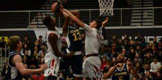 CSUN basketball players jump up to block opposing team's shot