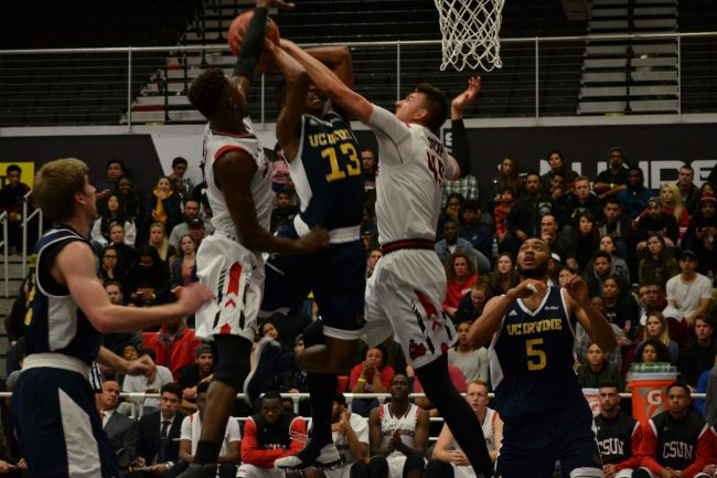 UC irvine player takes a shot at the basket and is blocked by two CSUN players