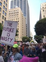 "Woman in protest holds sign which says, ""The future is nasty"""