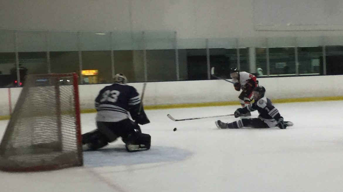 Quentin Abaya (15) shoots the puck on net as Jake Nelson (3) attempts to block and Jared Bussell (33) attempts to stop the puck from going in Saturday night at the Iceoplex in Simi Valley. Photo credit: Solomon Ladvienka