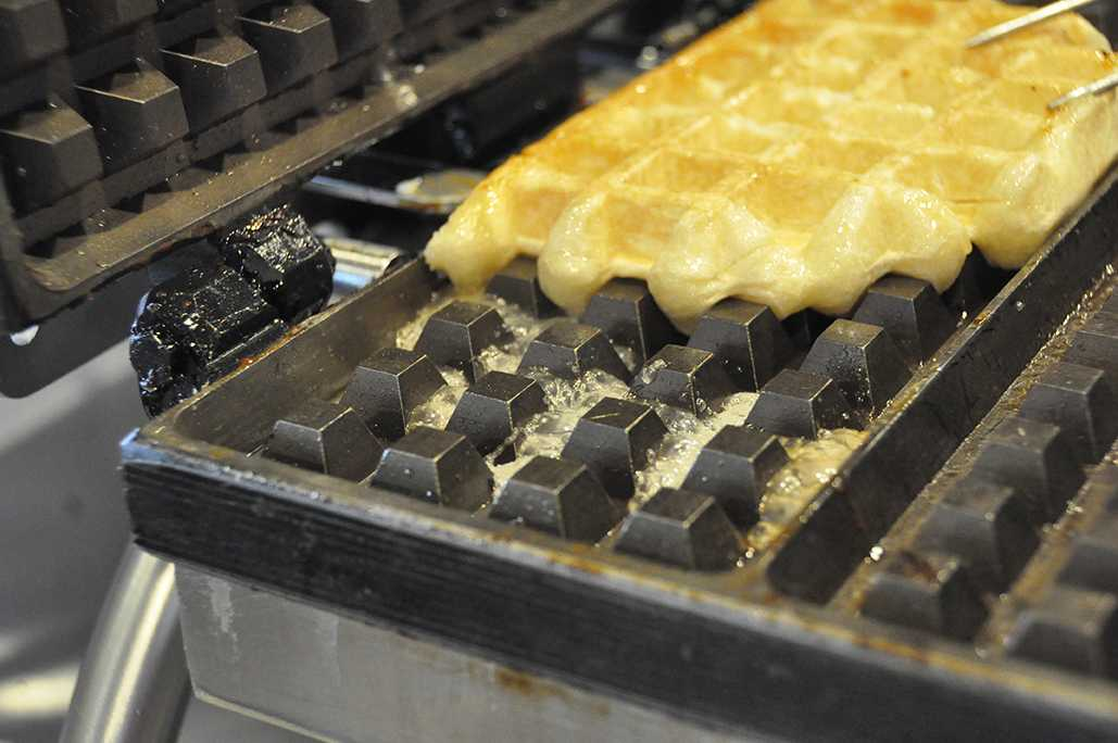As+Boyd+grills+the+plain+waffle+on+the+grill%2C+the+pearl+sugar+%28imported+from+Belgium%29+from+the+waffle+boils+which+creates+excess+caramel+on+the+surface.+%28Nathalie+Ramirez%29