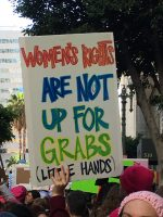 "Protester holds sign which says, ""women's rights are not up for grabs"""