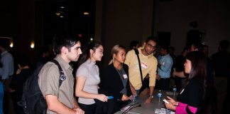 Students speak with an engineer at a booth