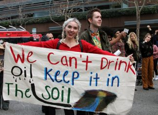 "Women holds cloth poster that says, ""we can't drink oil, keep it in the soil"""