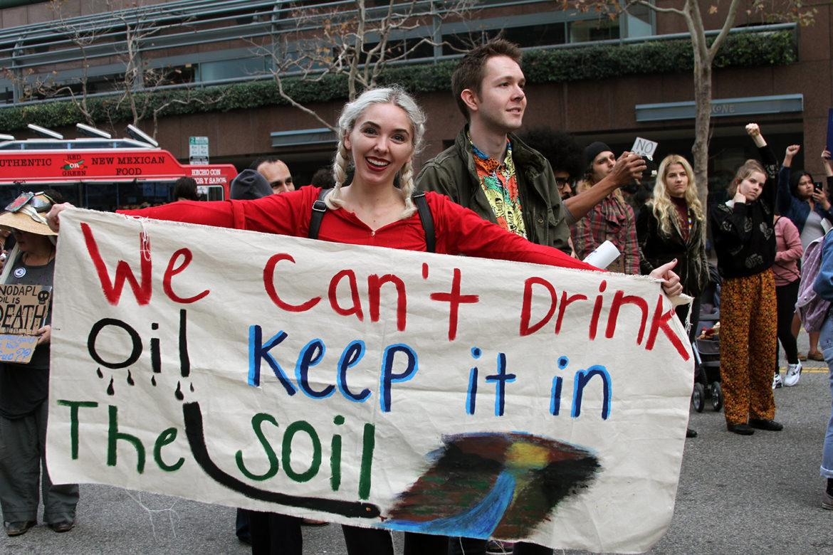 """Women holds cloth poster that says, """"we can't drink oil, keep it in the soil"""""""