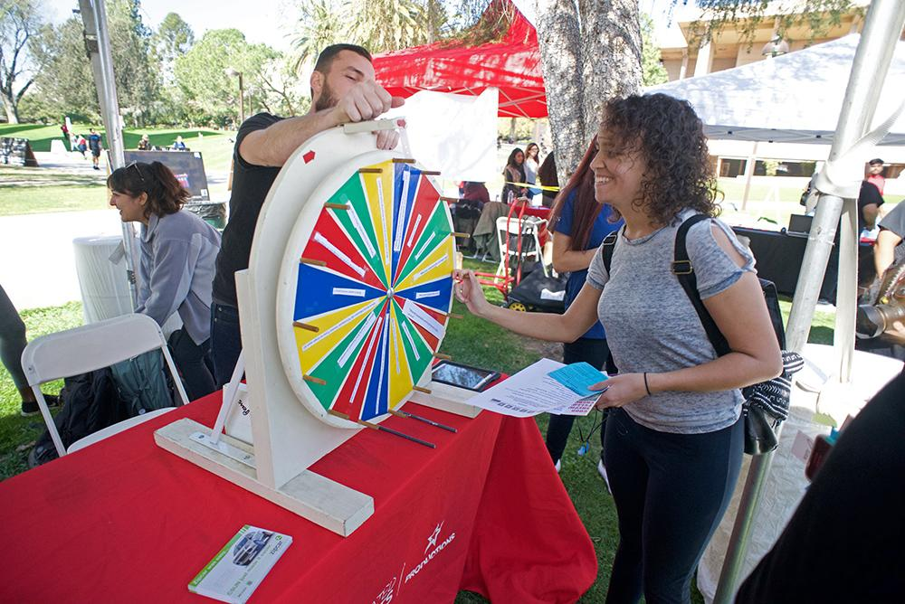 A member of the sustainability club plays a game with a csun student
