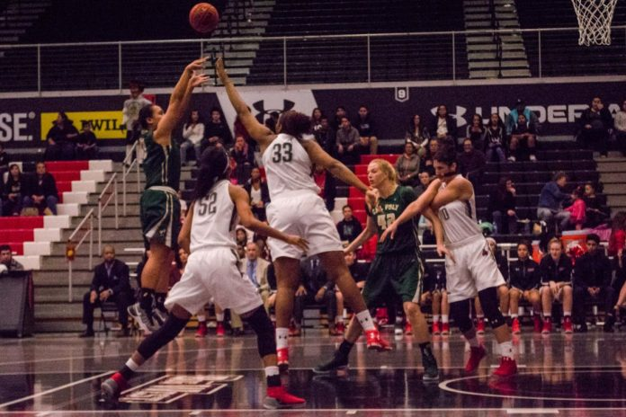 Photo depicts caly poly player taking a shot and csun players blocking