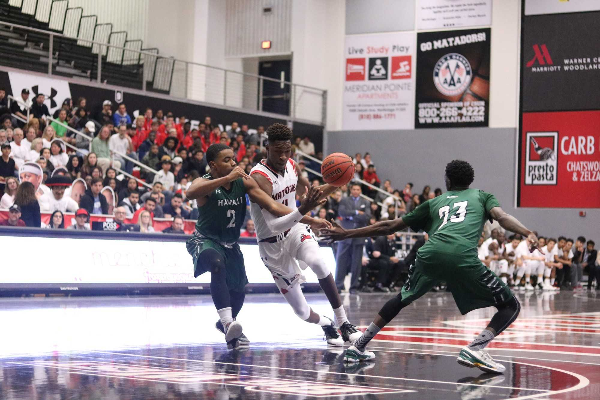 CSUN's junior forward, Tavrion Dawson, goes in for a layup while being double-teamed by Hawai'i's, Brocke Stepteau and Sheriff Drammeh (left to right), at the Matadome, on Saturday, February 4th. Photo credit: Lauren Valencia