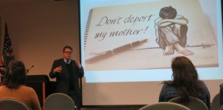 "Man gives a presentation with an image that shows a boy crying with text that reads, ""don't deport my mother"""