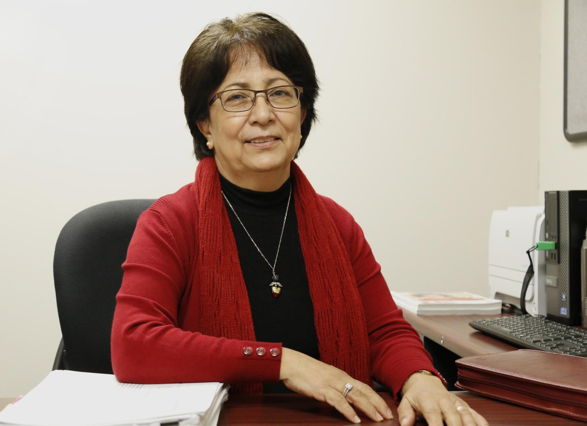 photo shows Juana Mora sitting at her desk