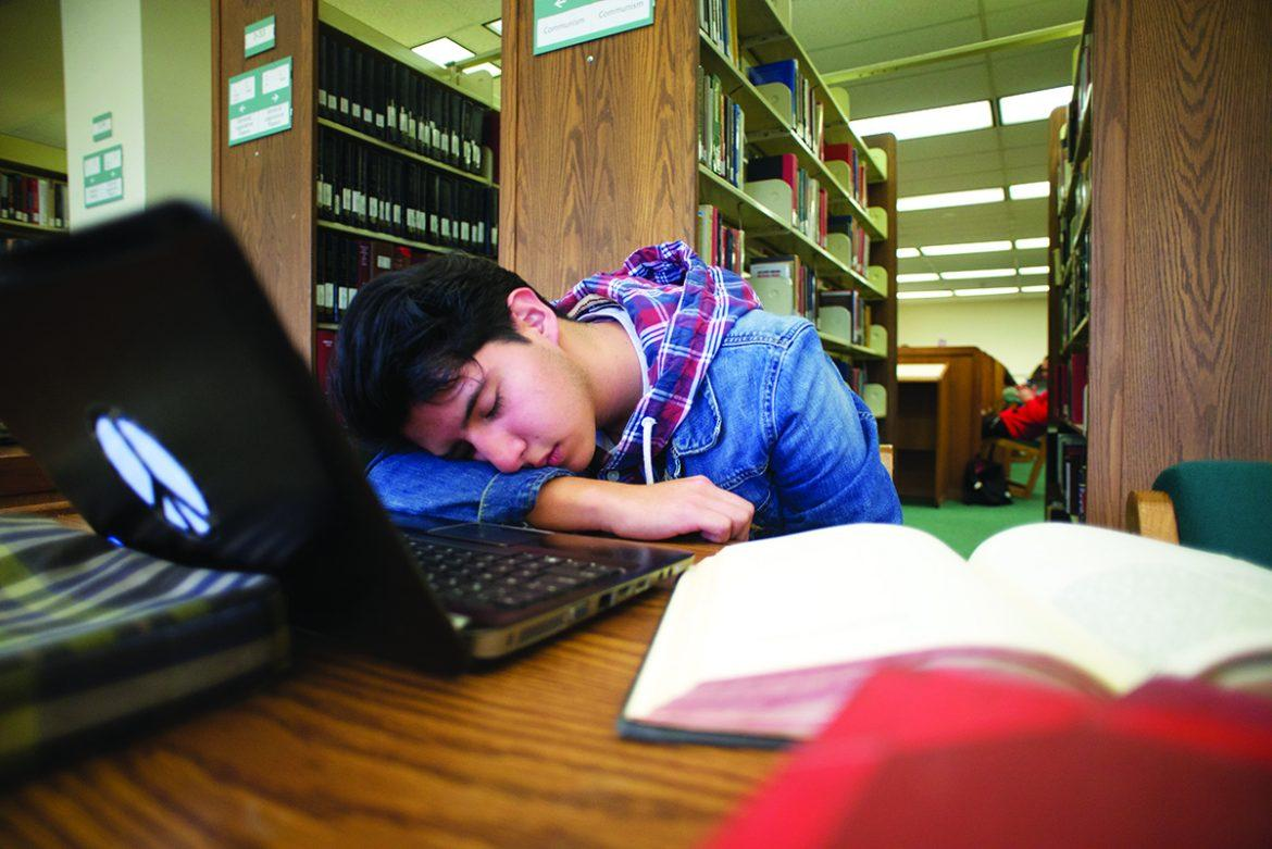 Photo+shows+a+student+napping+in+the+library