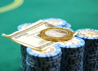 Poker chips are pictured with a 100-dollar bill