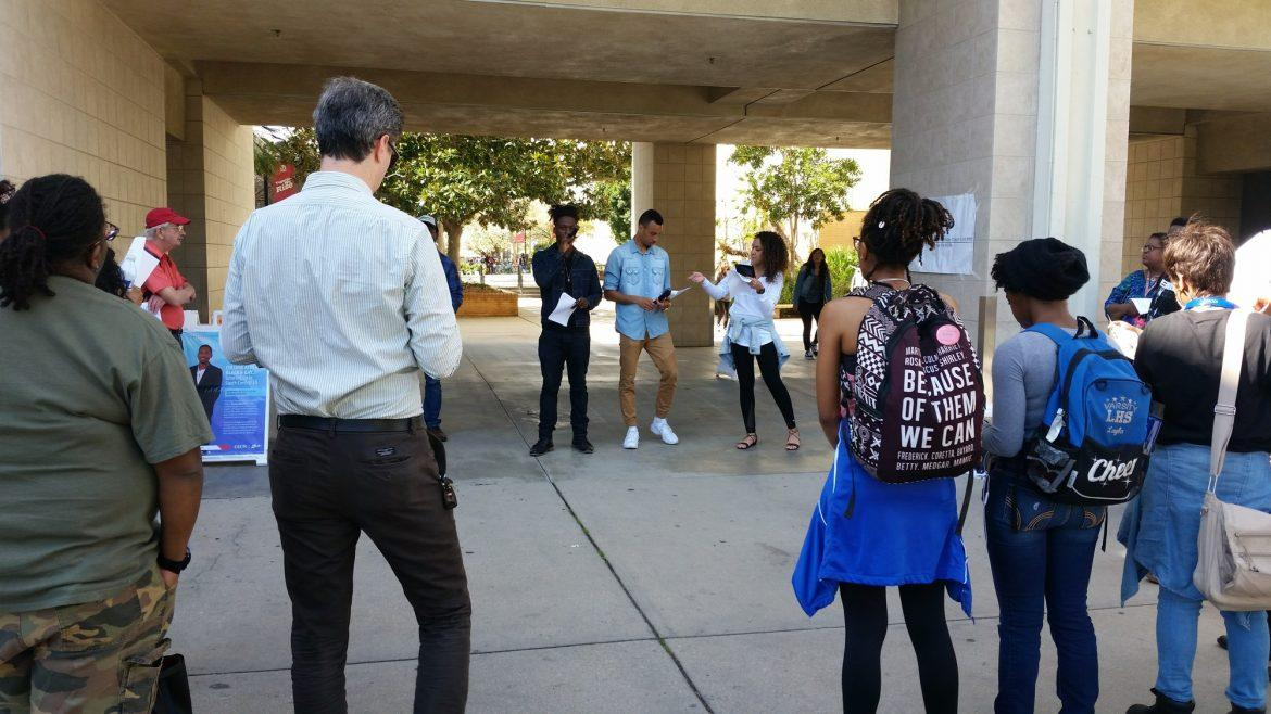 A group of students form a circle outside of sierra tower