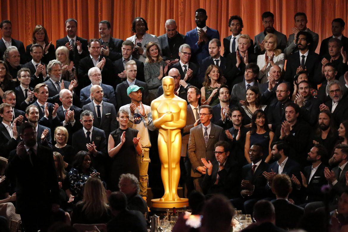 ACademy+Awards+nominees+are+all+gathered+around+a+giant+oscar