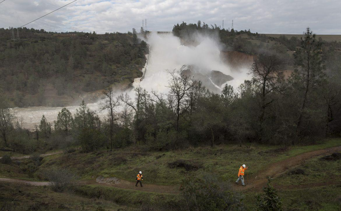 Two PG and E workers walk near the Oroville Dam