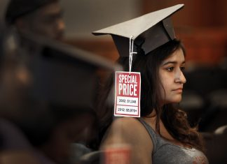 """Woman wears a graduation cap that says, """"special price 2002: 1,248 dollars 2012: 5,970 dollars"""""""