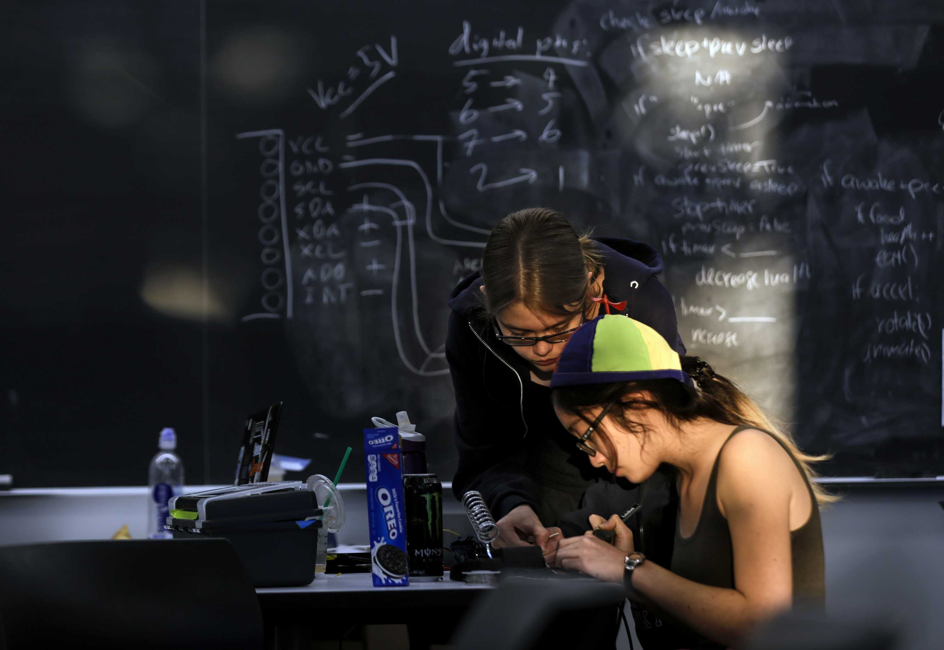 Morning sun hits Elizabeth Poss, 19, left, and Lauren Hu, 20, as they work on their group project