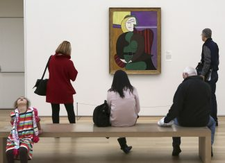"""Several people stand in front of picasso's """"red armchair"""" painting which appears to be an abstract image of a woman sitting in a chair"""