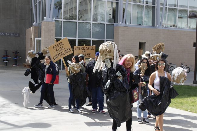 Art pieces representing environmental issues marched to Oviatt Library