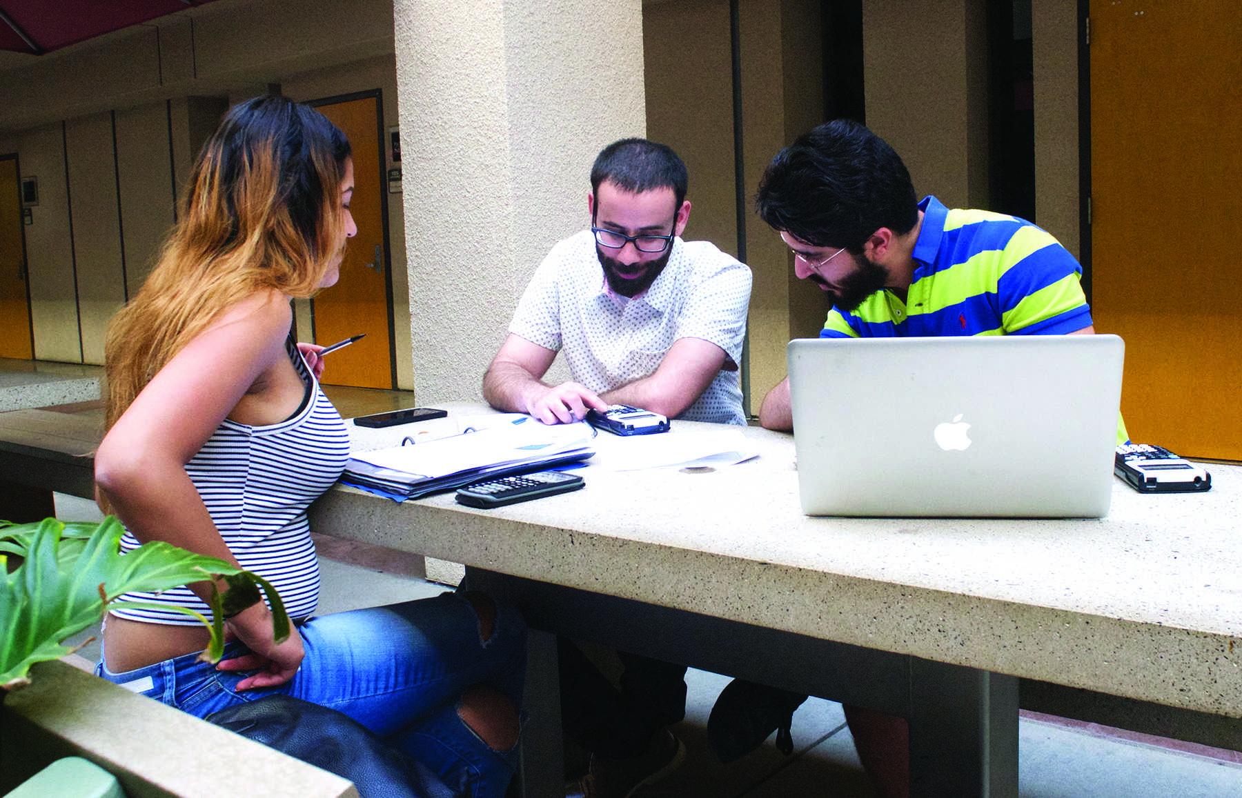 Senior supply chain management majors Kimberly Sanchez and Ibrahim Abduljibbar look at the calculator Joshua Rodgers it using to solve a problem for their homework. Photo credit: Alejandro Aranda