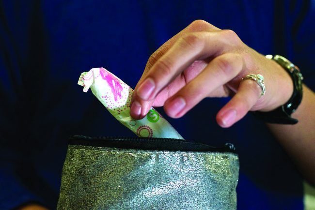 Photo shows a woman taking a tampon out of her clutch
