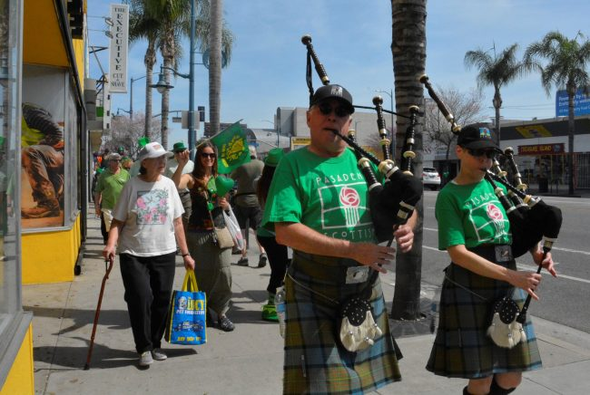 Couple wearing matching kilts play their bagpipes in Pasadena