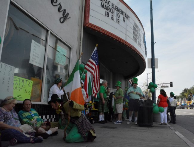People dressed up for St. Patrick's day wait outside the theater