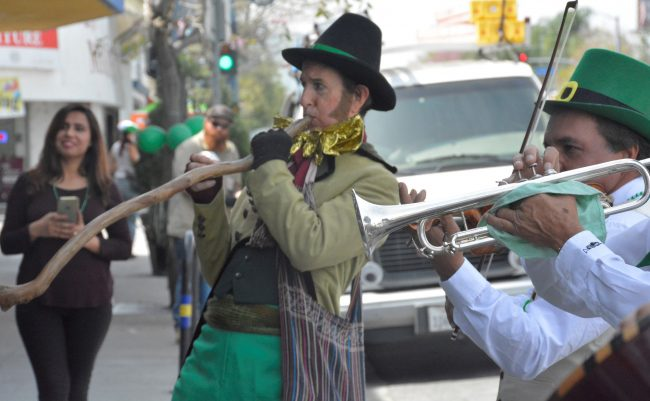 People dressed in festive green clothing play instruments for St. Paddy's day