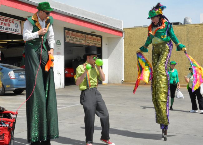 performers walk on stilts, blow balloons, and juggle in the streets of Pasadena