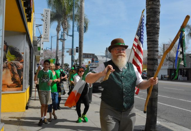 Thomas, an old man wearing a green vest and hat with green detailing, leads the march followed by several people all wearing green