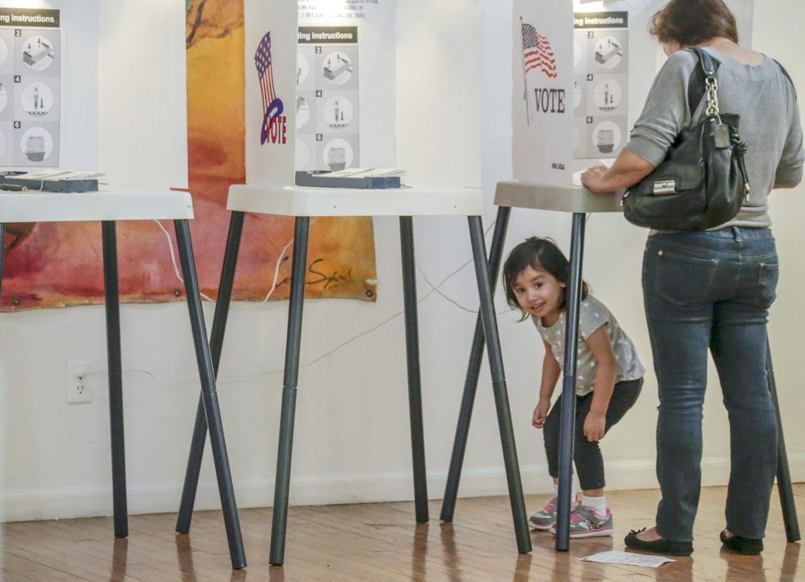 Little girl stands underneath the voting booth while her grandmother votes