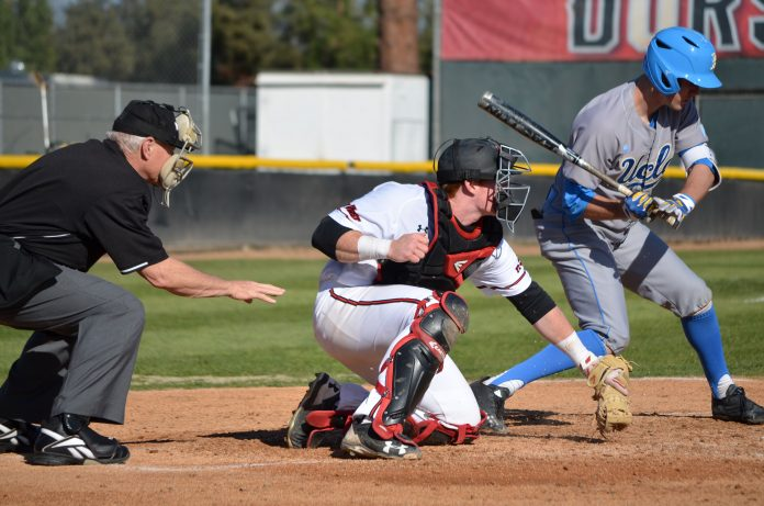 UCLA batter misses the ball