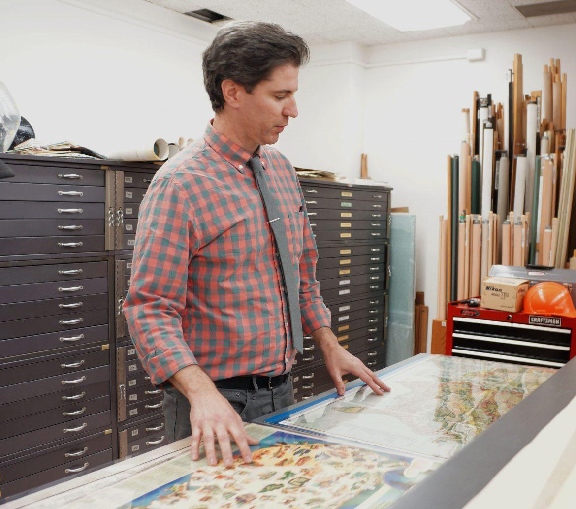 Chris Salvano is the map curator and librarian at the map library in Sierra Hall 165 and has been at CSUN for two years. He is showing a student the variety of the maps archived in this room. Photo credit: Katarina Karapetyan