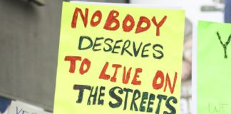 "woman protests with poser that reads, ""nobody deserves to live on the streets yes on H"""