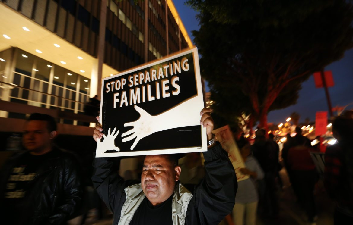 Man+holds+up+a+poster+that+reads%2C+%22Stop+separating+families%22