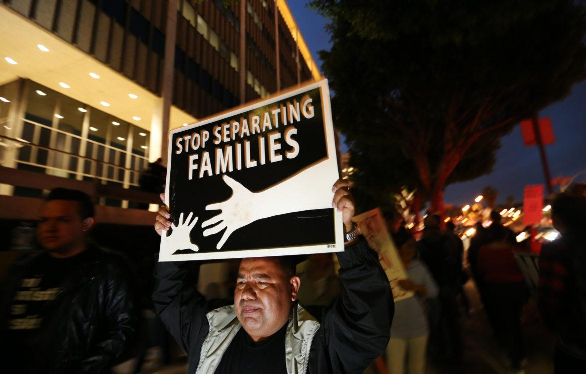 """Man holds up a poster that reads, """"Stop separating families"""""""