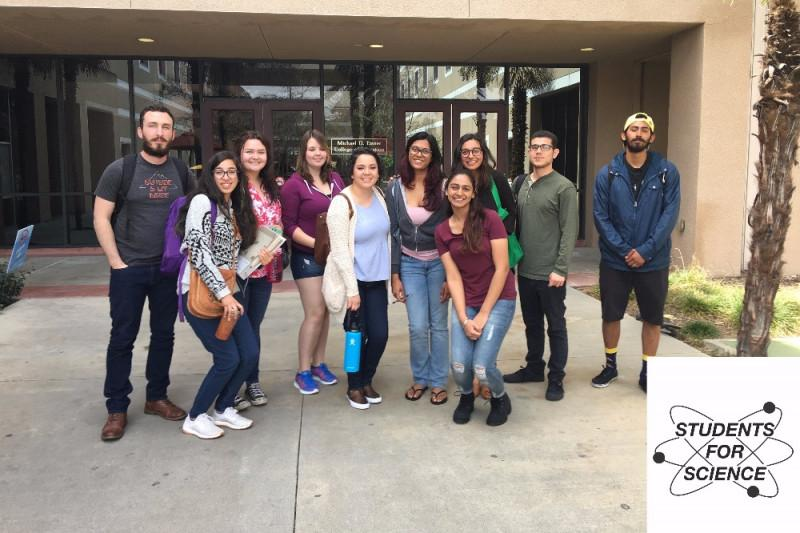 members+of+students+for+science+pose+for+a+photo+outside+of+the+education+building