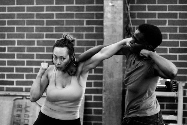 Photo shows two women practicing their punches on one another