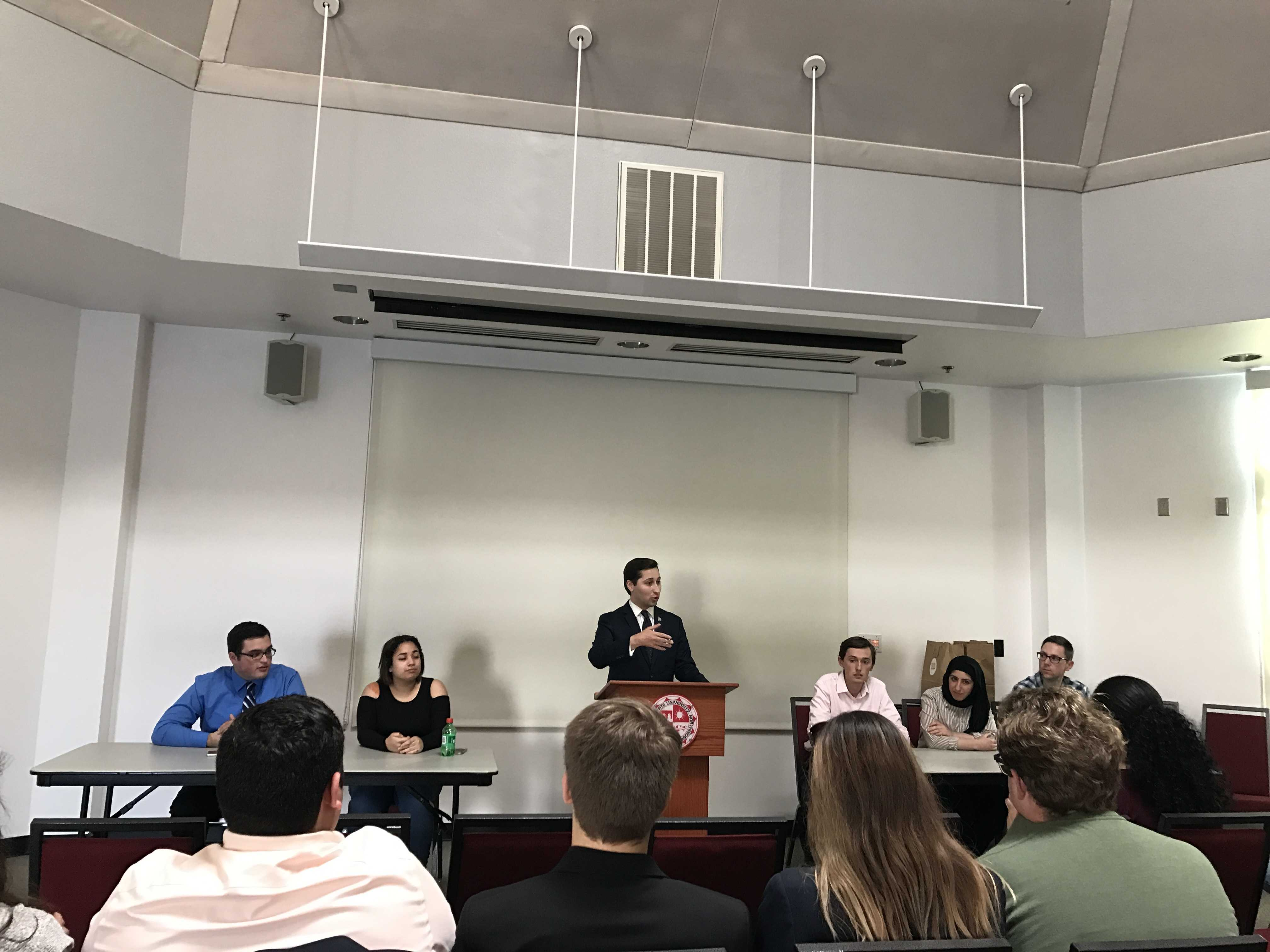 Sean Regan pictured presenting for a small crowd with a panel