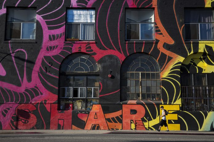 Man walks past building covered in a rainbow mural that says,
