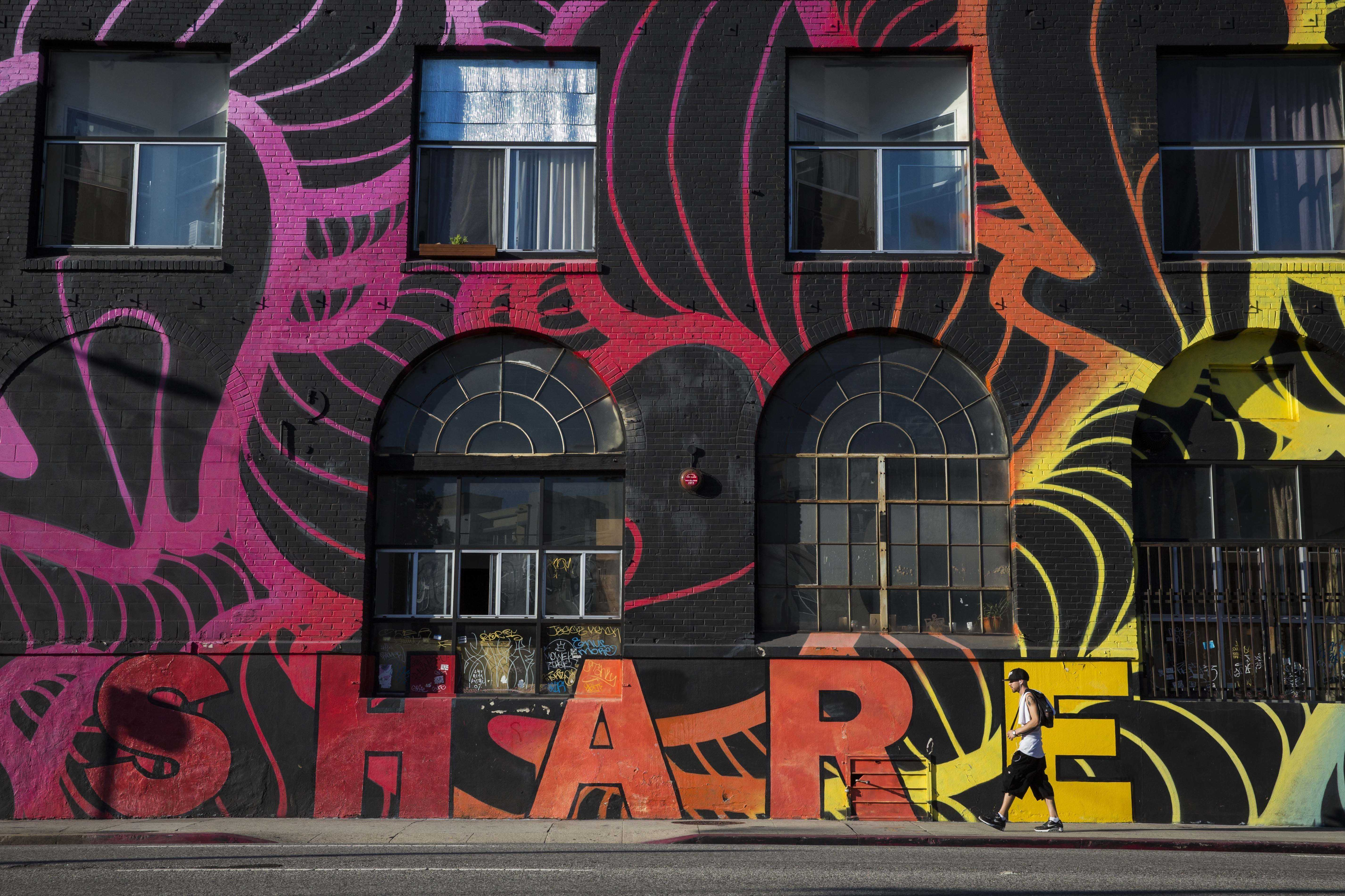 """Man walks past building covered in a rainbow mural that says, """"share"""" and features an abstract design"""