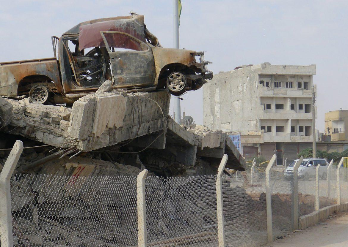 photo+shows+the+aftermath+of+the+battle+of+Kobani+with+a+destroyed+car+pictured+on+top+of+a+collapsed+structure