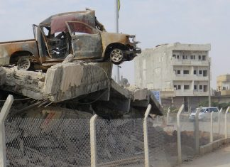 photo shows the aftermath of the battle of Kobani with a destroyed car pictured on top of a collapsed structure